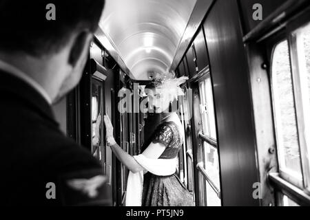 Portrait of beautiful woman in vintage tea dress standing in corridor of locomotive train as air force officer in uniform watches her - Stock Image