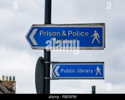 Direction signs in Queen Street Ripon directing pedestrians to the Prison and Police Museum and the Public Library - Stock Image