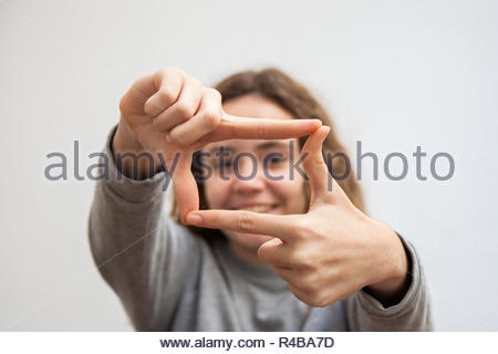 Teenage girl frames with her hands as photographers and filmmakers do - Stock Image