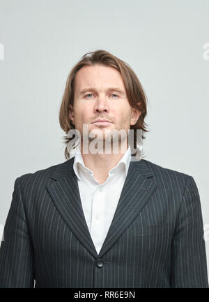 The handsome men in black suits on a white background, looking in a camera, a white shirt, brutal man with long curly hairs, business man, very stylis - Stock Image