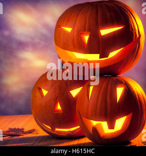 Halloween pumpkins still life, three carved gourds with glowing creepy faces on the table, traditional Halloween - Stock Image