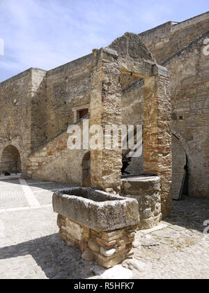 The hilltop town of Miglionico in Basilicata, Southern Italy with the Castello Malconsiglio and a water trough in the courtyard - Stock Image