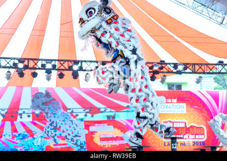 Practitioners in costume lion dancing perform on stage in Van Lang Park, District 5, to pray, safety and luck in new year attract visitors to see - Stock Image