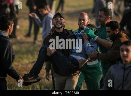 Gaza City, The Gaza Strip, Palestine. 19th Apr, 2019. A Palestinian medic carrying wounded protester east of Gaza city during friday clashes, at least 46 Palestinians including medics and journalists were injured by Israeli troops. Credit: Abed Alrahman Alkahlout/Quds Net News/ZUMA Wire/Alamy Live News - Stock Image