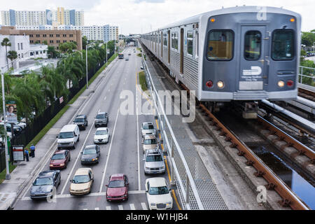 Miami Florida NW 12th Avenue Metrorail public transportation mass transit approaching train elevated track parallel street car t - Stock Image
