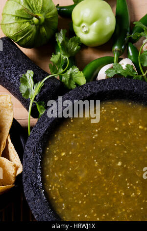 Stock image of mexican salsa verde on mortar and pestle with ingredients - Stock Image