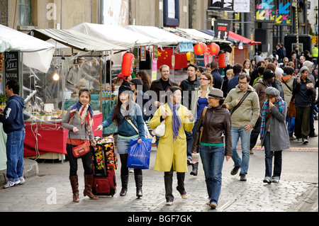 Visitors passing ethnic food street vendors at UpMarket in the Old Trueman Brewery. London. Britain. UK - Stock Image