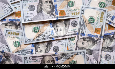 Background of lots of banknotes of 100 dollars spread on a surface, concept for poor and wealthy, uprising and declining economy - Stock Image