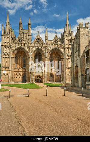 The ornate west front of Peterborough Cathedral bathed in sunshine against a blue sky. - Stock Image