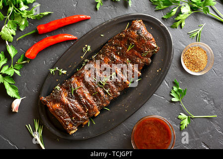 Grilled spare ribs on plate over black stone background. Tasty bbq meat. Top view, flat lay - Stock Image