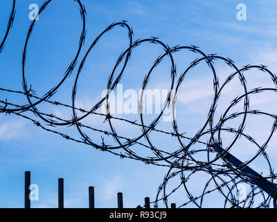 Razor wire against blue sky and clouds. - Stock Image