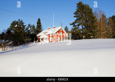 old red cottage in a snowy winter landscape - Stock Image