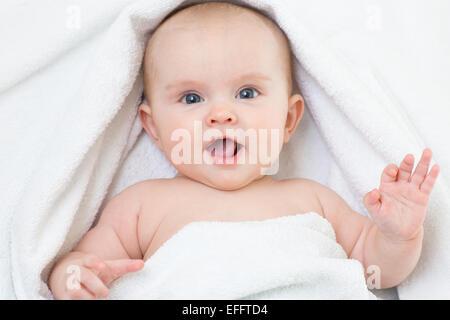 Cute smiling baby portrait lying on bathing towel - Stock Image