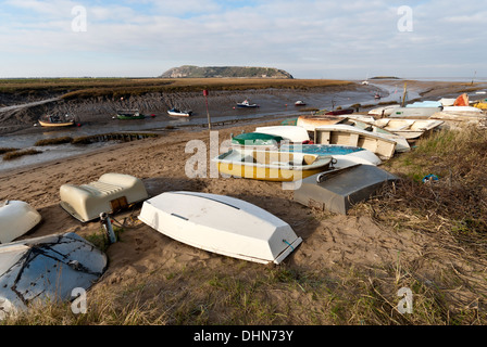 Small boats along the shore of the River Axe at Uphill at low tide. - Stock Image