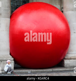 Giant 15-foot red inflatable ball by artist Kurt Perschke, RedBall Project, in Covent Garden Piazza, London, England, - Stock Image