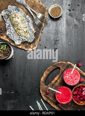 Healthy lunch of chicken fillet and berry smoothie. On black background. - Stock Image