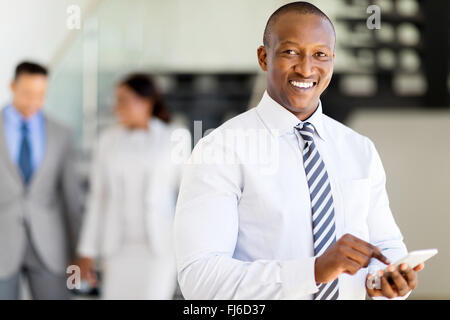 portrait of modern African businessman texting on cell phone - Stock Image