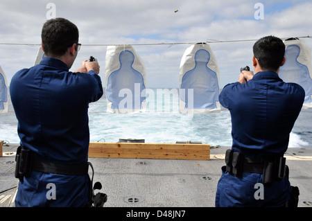 Sailors fire M9 pistols at sea. - Stock Image