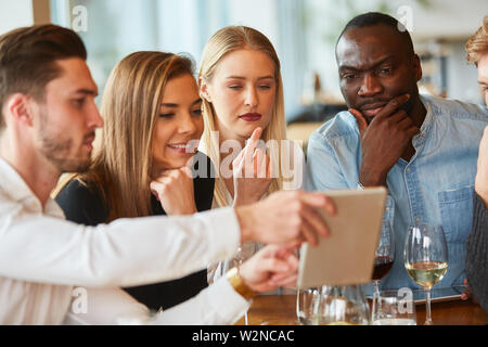 Group of friends in the restaurant looks anxiously at a tablet computer - Stock Image