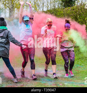Three women runners being covered in paint on Macmillan cancer charity 5K color fun run. - Stock Image