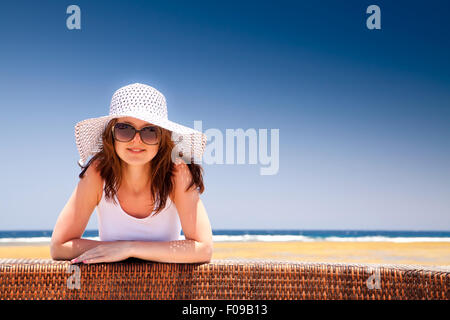 The young beautiful girl in a hat on vacation, on a sunny beach - Stock Image