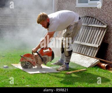 Stone paving slab being cut with a circular petrol powered saw by uk builder - Stock Image