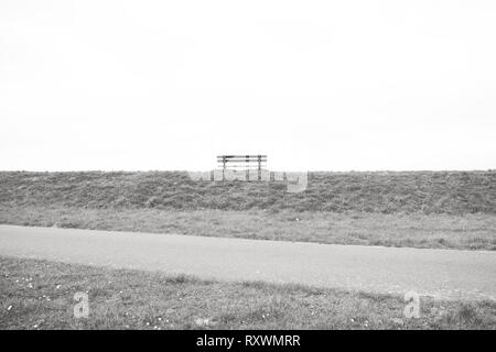 A single empty wooden bench on the horizon - Stock Image