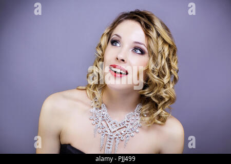 Young woman caught in evening dress, looking up, on the side - Stock Image