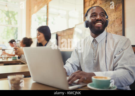 Smiling young man with headphones using laptop and drinking coffee at cafe table - Stock Image