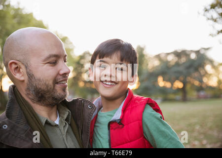 Portrait happy father and son in autumn park - Stock Image