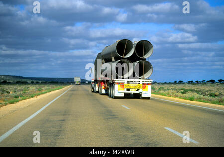Road train transporting large water pipes, Australia - Stock Image