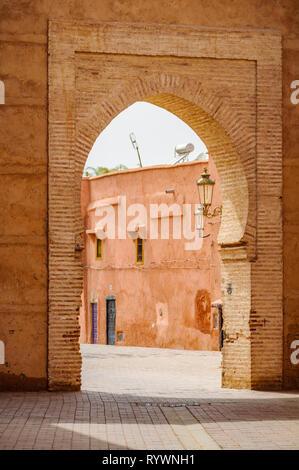 Empty street through a gate in the Medina of Marrakech, Morocco - Stock Image