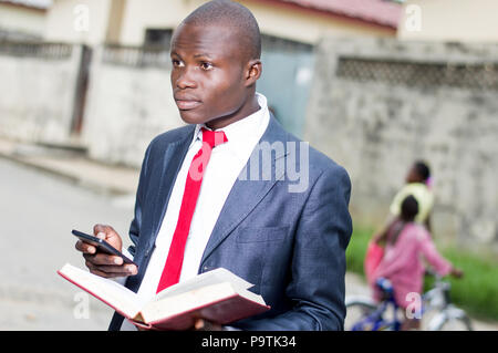 Young businessman with an open book in his left hand and manipulating a portable phone in his right hand - Stock Image