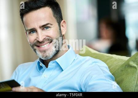 Businessman sitting in hotel lobby - Stock Image