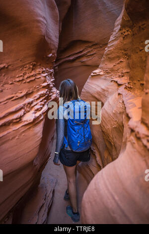 Rear view of female hiker with backpack walking amidst canyons - Stock Image