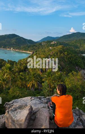 Thai girl sit on rocky cliff of John-Suwan viewpoint, Ko Tao island - Stock Image