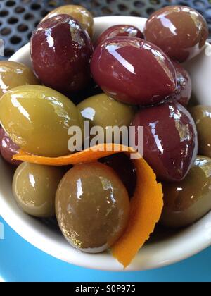 Olives in a bowl with orange zest - Stock Image