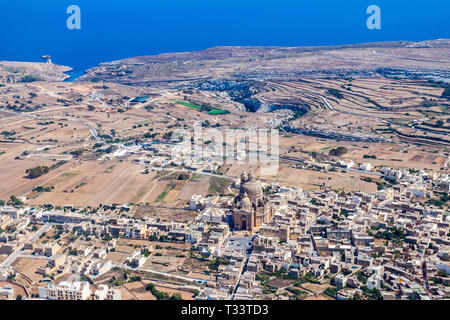 The rotunda of Xewkija, Casal Xeuchia is the largest in Gozo and its dome dominates the island everywhere. Mgarr ix-Xini bay in background. Rural Gozo - Stock Image