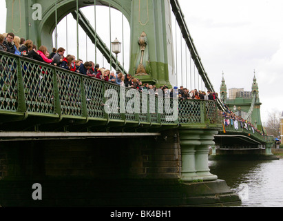 Spectators Watching the Head of the River Race on the River Thames from Hammersmith Bridge. - Stock Image