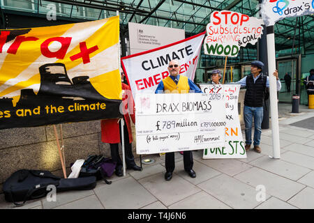 London, UK. 17th April 2019. AxeDrax protesters at the Dept of Business (BEIS) demand an end to subsidies to Drax for burning wood. Drax power station, the UK's biggest carbon emitter, with over 13m tonnes of CO2 from burning wood in 2018, subsidised from our electricity bills for £789m in 2018 despite its huge contribution to climate change. They call for proper carbon accounting to end rewarding polluters, an end to plans for burning gas at Drax and for subsidies to encourage genuine renewables including solar and onshore/offshore wind and more grants for home insulation. - Stock Image