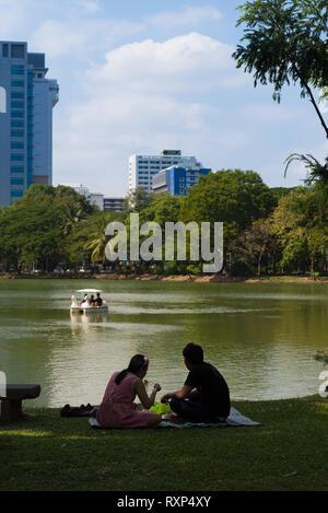 Tourists having a picnic near a lake in Lumpini park, Bangkok, Thailand - Stock Image