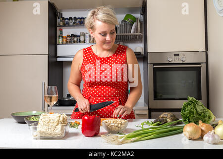 Tortoise eating salad while young girl looks at him and cuts carrot - Stock Image