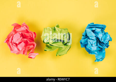 pink, blue and green crumpled paper balls on bright yellow background. concept of idea, recycle and stress - Stock Image
