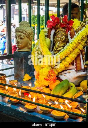 Candles, Garlands, and Offerings at Shrine in Sree Veera Hanuman Hindu Temple, Kuala Lumpur, Malaysia. - Stock Image