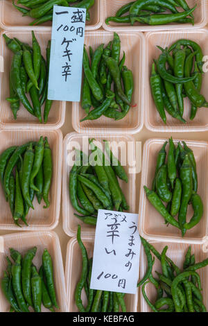 Punnets of small fiery fresh green chillies for sale on a market stall in Japan - Stock Image