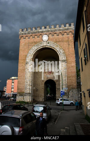 one of the gates to enter the city of siena, italy with a moody dark stomy sky behind it but sunlight on the entrance way - Stock Image