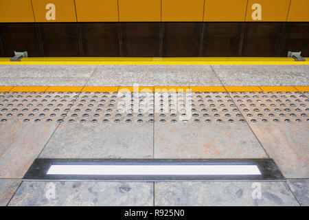 tactile paving also called detectable warning surfaces to assist visually impaired pedestrians, no people, safety warning lamp - Stock Image