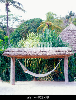 An empty hammock awaits a guest  at Young Island resort. Kingstown, St. Vincent. - Stock Image