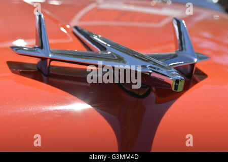 Westbury, New York, USA. June 12, 2016. Chrome Flying Bird Rocket Eagle hood ornament is seen in close up on red - Stock Image