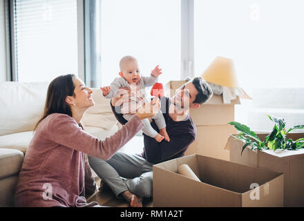 A portrait of young couple with a baby and cardboard boxes moving in a new home. - Stock Image
